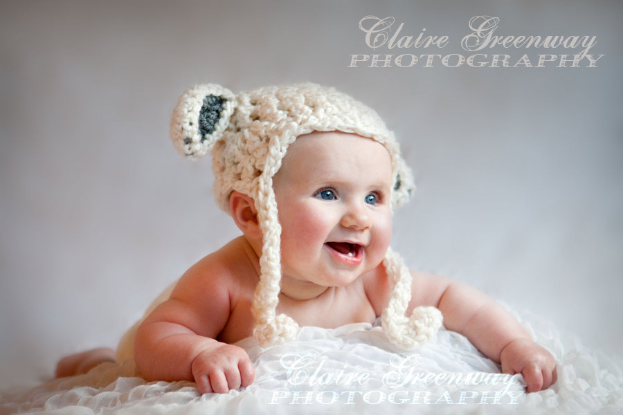 Surrey baby photography portrait session of smiling baby pictured in knitted lamb hat in natural light