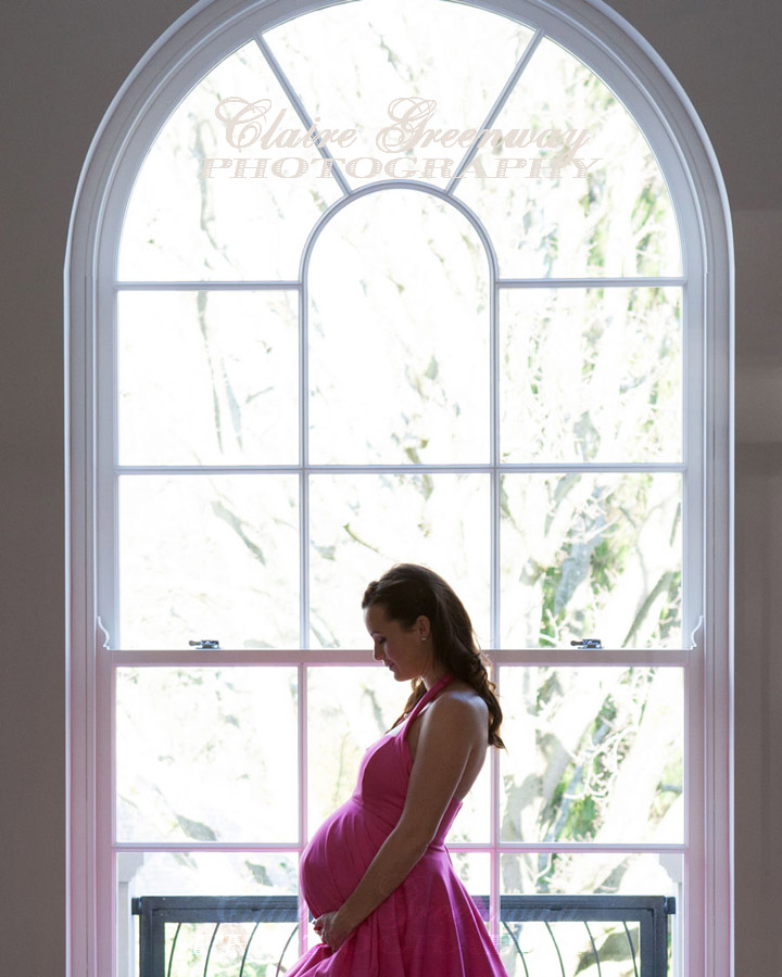 Maternity bump portrait of mum-to-be prior to photography coverage of Baby Shower party near London in Surrey in front on a large window backlit with natural, window light