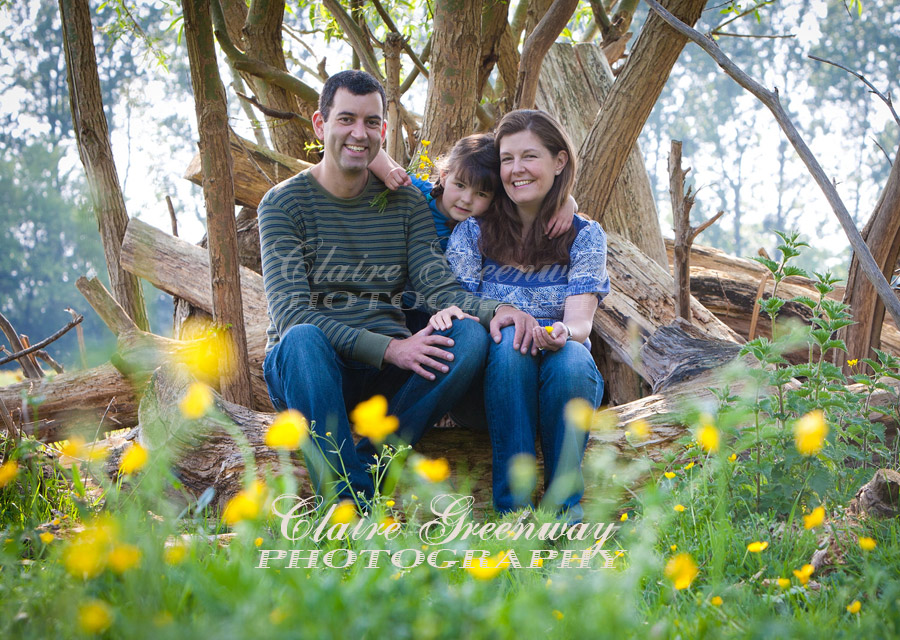 A family portrait photograph of smiling parents and child surrounded by green summer or spring leaves, buttercup flowers and tree foliage, photographed in natural light sunshine of the late afternoon in editorial portraiture lifestyle style.
