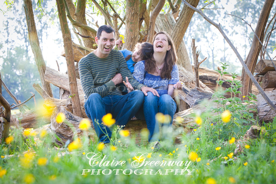 A family portrait photograph of smiling, laughing parents and child surrounded by green summer or spring leaves, buttercup flowers and tree foliage, photographed in natural light sunshine of the late afternoon in editorial portraiture lifestyle style.