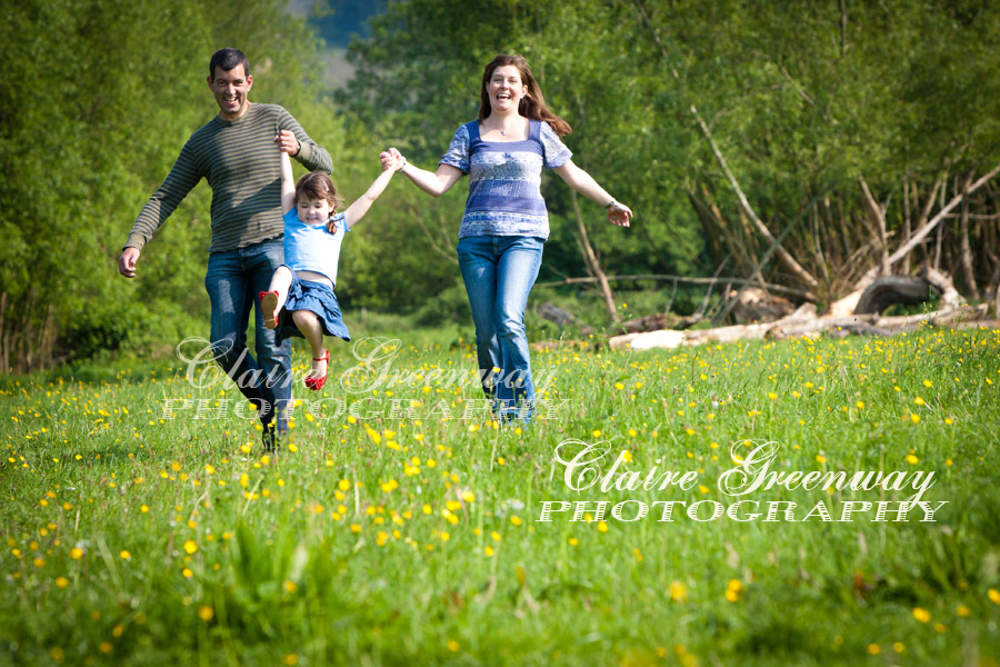 A family portrait photograph of smiling, laughing parents swinging their child as they walk through a field of green grass and buttercup flowers, photographed in natural light sunshine of the late afternoon in editorial portraiture lifestyle style.