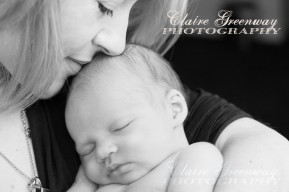 A mother cuddles her sleeping newborn baby girl in her arms in a close cropped black and white portrait photograph shot using natural window light
