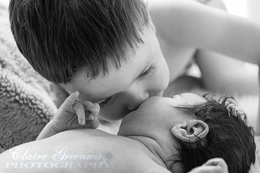 Newborn baby girl is kissed by her older brother in a black and white photograph during a child photography portrait session at home in NW London.