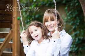 A mother smiles with her daughter as they sit on a swing during a family portrait session in North London