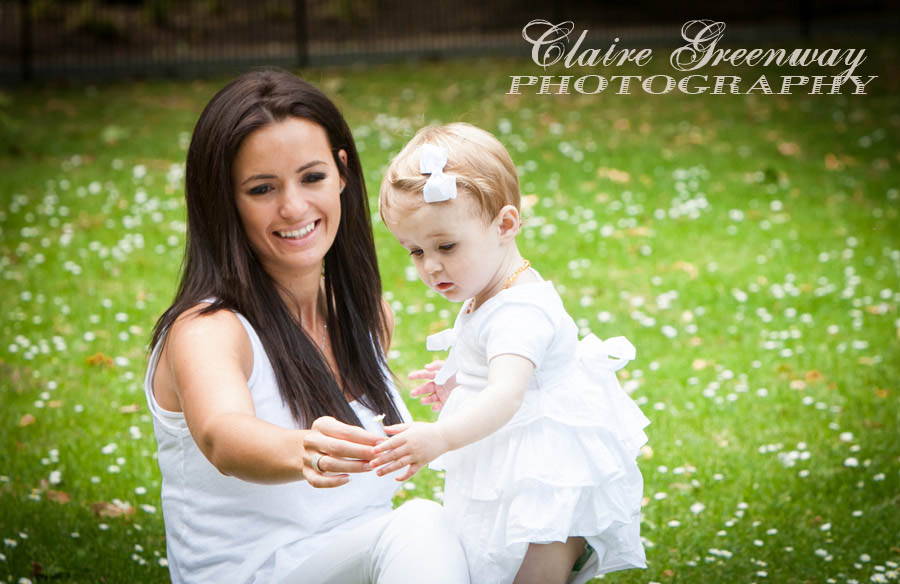 A mother gives her toddler daughter a flower during an outdoor family photography session in South West London