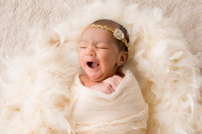 newborn baby yawns as lies on fur and feathers in golden, creamy tones for a portrait session in London