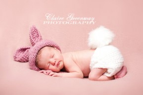 newborn baby in a bunny hat and fluffy tail for a springtime baby photography shoot in Surrey